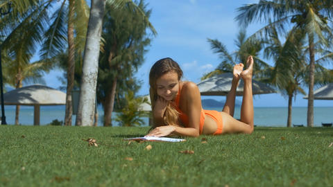 Nice Girl in Swimsuit Reads on Grass among Palms Footage