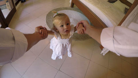 POV of a cute young baby girl taking her first walking steps with her father Footage