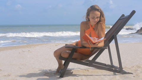 Blonde Girl Sits in Deck-chair with Diary on Beach Footage