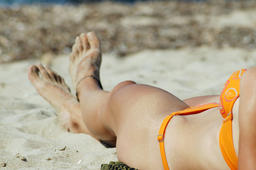 Young woman legs sunbathing on the beach Photo