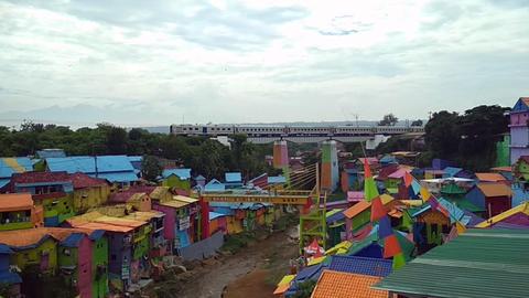 Passenger train passing over Kampung Warna Warni Jodipan or colorful village Footage