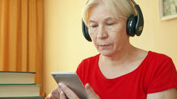 Senior woman uses application for listening skills training, learning foreign Footage