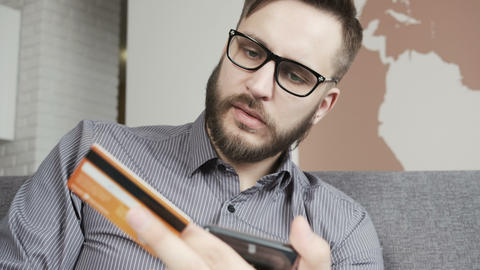Man paying online by bank card at smartphone Image