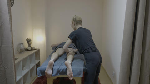 Skinny blonde masseuse with eyeglasses carefully massaging the legs of a man in Live Action
