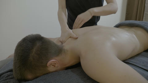 Close up of a young female masseuse doing a detensioning and relaxing massage to Footage