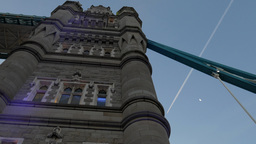 Close pan across one tower of Tower Bridge on a clear day with airline contrails Footage