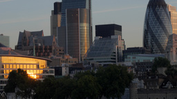 Camera tilts up from the River Thames to the skyscrapers on the City of London o Footage