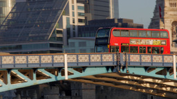 Camera tracks a red London bus passing over Tower Bridge on a sunny autumn morni Footage