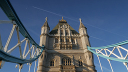 Pan across the south tower of Tower Bridge looking up. Contrails are seen in the Footage