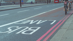 Two cyclists on Boris Bikes cross London Bridge in a bus lane. Footage is 4K Footage