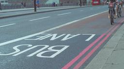 Two cyclists on Boris Bikes cross London Bridge in a bus lane. Footage is 4K Footage