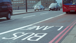 Red London bus drives along bus lane on London Bridge. Close shot in 4K Footage