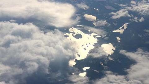 Beautiful view under wing. Shining sun lake, islands, forest, mountains Footage