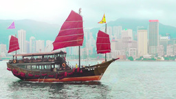 Junk boat with red sails is in Victoria Harbour, Hong Kong Footage