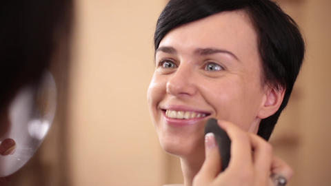 The make-up artist applies a tonal cream with a big sponge on the face of a Footage