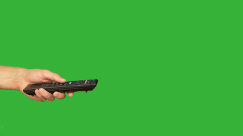 Male left hand pushing buttons on remote controlon green chroma key background Image