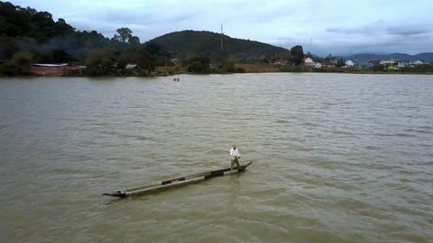Person in Hat Sails Boat on Lake against Rural Area Live Action