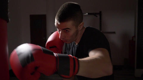 Muscular boxer throwing punches in the boxing bag in a darken sport gym in slow Footage