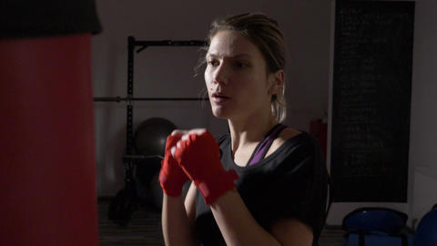 Motivated blonde female model hitting the punching bag without boxing gloves to Footage