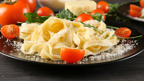 Black plate with tagliattele pasta with parmesan cheese on Footage