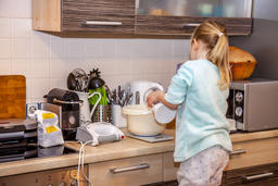 Little girl baking waffles in the kitchen following a recipe on the smartphone Fotografía