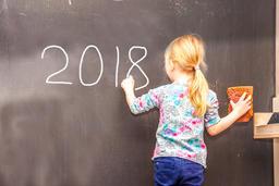 Cute little girl writing 2018 on chalkboard Fotografía