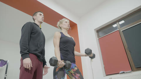Young attractive mother working out in a gym with dumbbells and a personal Footage