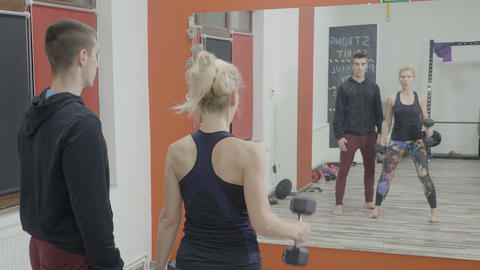 Woman working out intensely with weights to stay in shape and get over Footage