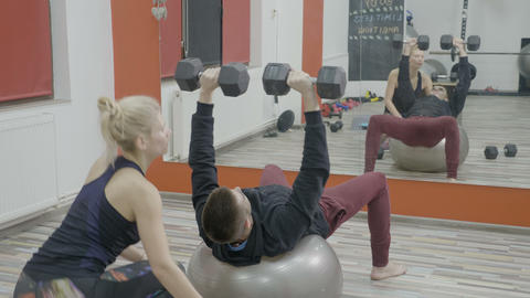Young husband exercising on a pilates ball with dumbbells to recover after Footage