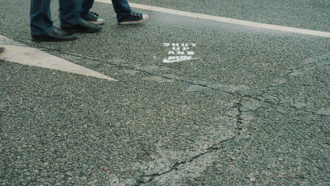 Feet of people walking on wet asphalt with road marking Footage