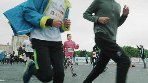 Young kids running marathon in crowd showing thumbs up Footage