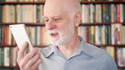 Modern senior man at home talking on cellphone via messenger app. Bookcase Footage