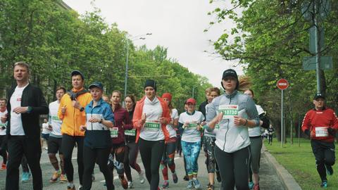 Elder man run on lawn to overtake crowd jogging marathon Footage