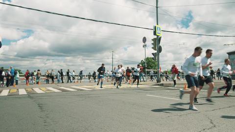 Sportive people running marathon around metal fencing at city crossroad Footage