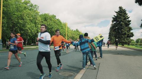 Line of cheerful kids gives high five to marathon athletes Footage