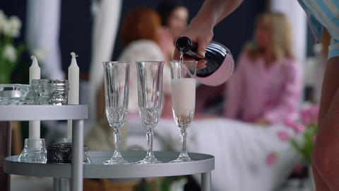 Close-up of a beautiful girl fills with champagne glasses for girlfriends who Footage