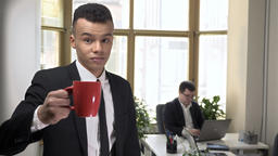 Young successful African businessman drinks coffee from a mug, looking at the Footage