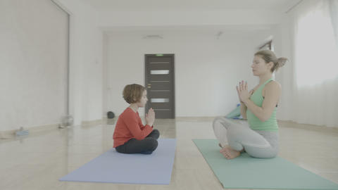 Young beautiful woman teaching yoga poses to a little child girl and how to Footage