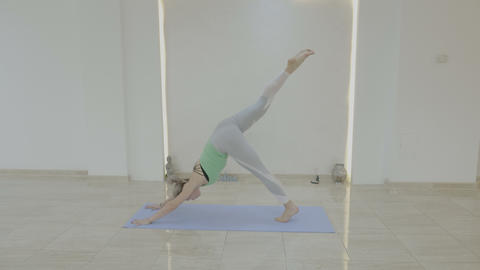 Young beautiful model woman exercising various yoga poses on a mat and Footage