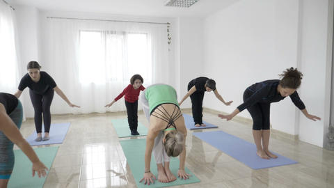 Little girl kid attending her first yoga class with her mother and other middle Footage