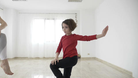 Beautiful fit female instructor teaching a little girl standing still yoga poses Footage
