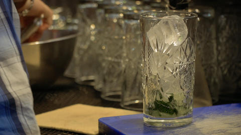 Bartender put cubes of ice into cocktail glass Footage