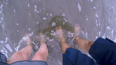 POV of the small waves crashing over a man and woman's bare feet standing in the Footage