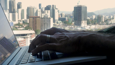Male hands typing on a laptop computer overlooking a modern busy city - slow Footage