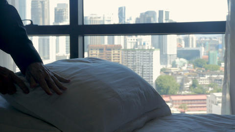 Person smoothing out pillows for a freshly made bed overlooking a modern city in Footage