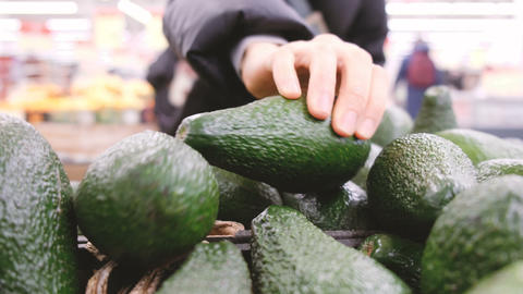 Woman chooses a ripe avocado in store Stock Video Footage