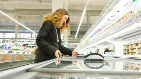 Girl chooses a frozen product in the refrigerator in the store Live Action