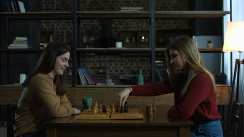 Two cheerful young women playing chess at home Archivo