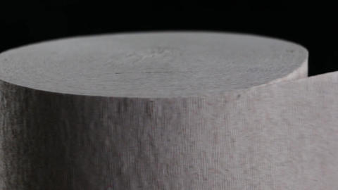 Toilet paper roll rotating on black background Footage