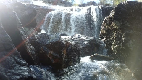 The waterfall shot against the sun silver dust Footage